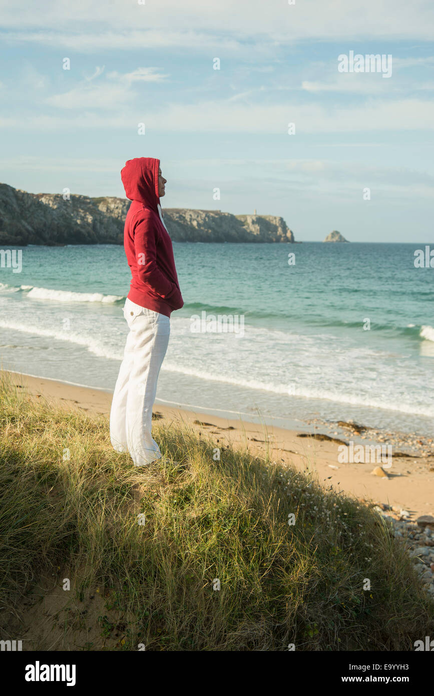 Mature woman standing gazing at sea view, Camaret-sur-mer, Brittany, France - Stock Image