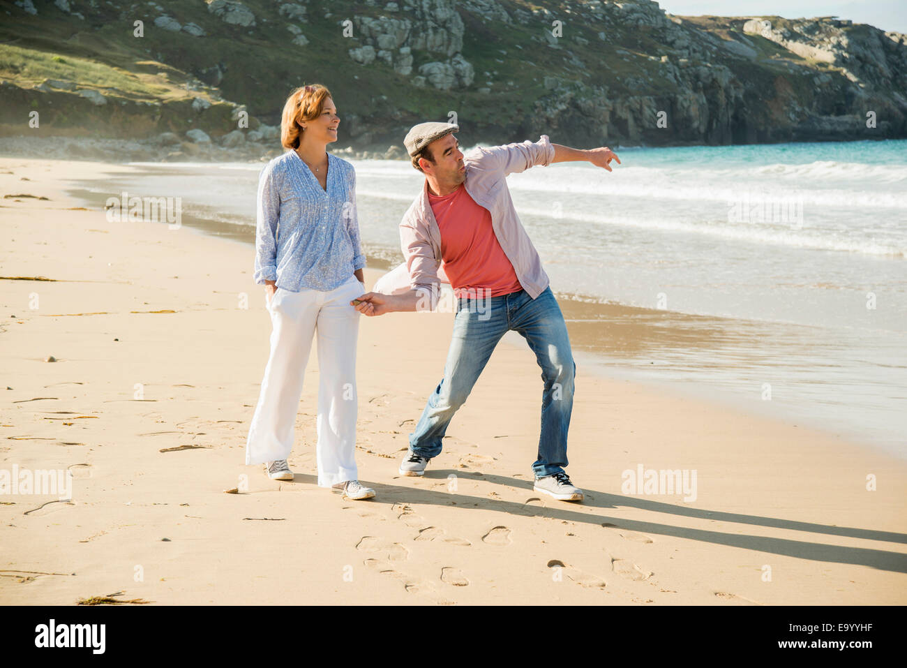 Mature couple throwing pebbles out to sea, Camaret-sur-mer, Brittany, France - Stock Image