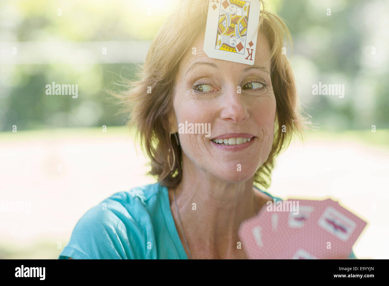Mature woman playing cards, a playing card stuck on her forehead - Stock Image