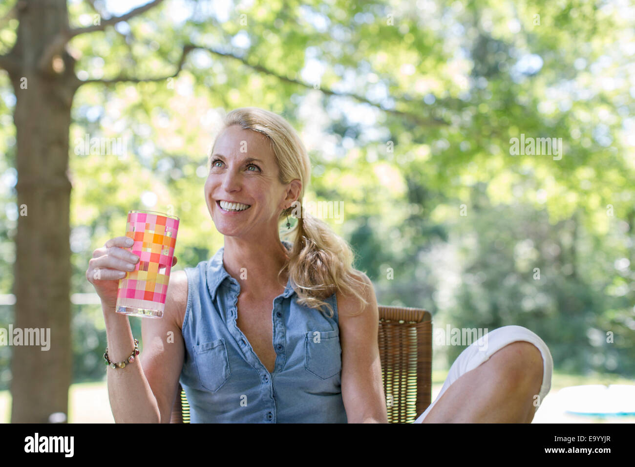Mature woman sitting in garden with drink - Stock Image