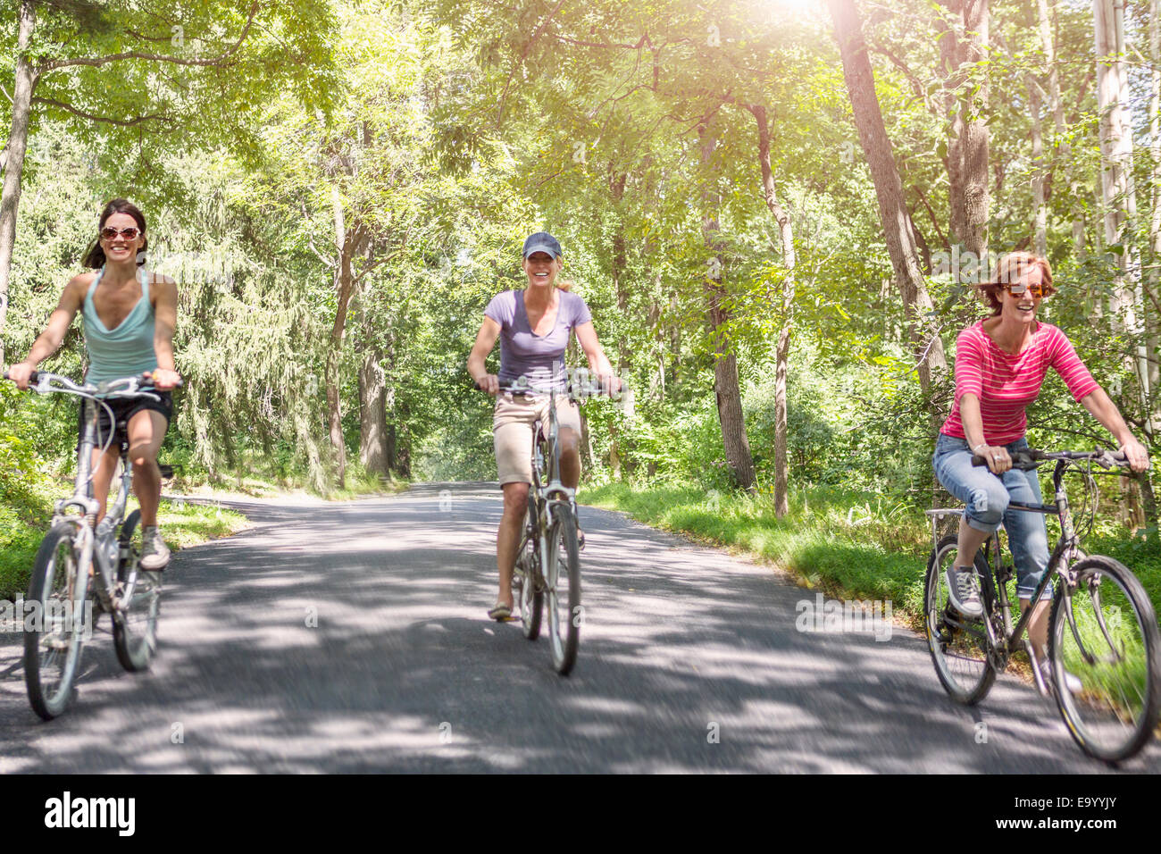 Three mature woman riding bicycles along country road - Stock Image