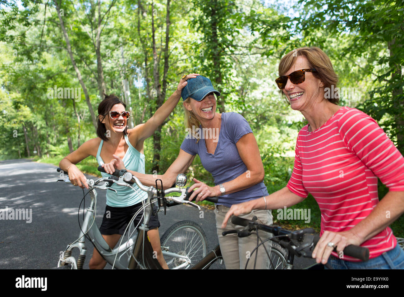 Three mature woman with bicycles along country road - Stock Image