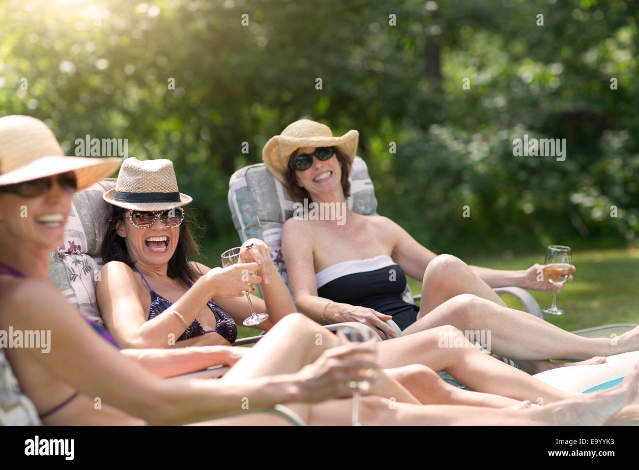 Three mature women relaxing in sun loungers, drinking wine - Stock Image