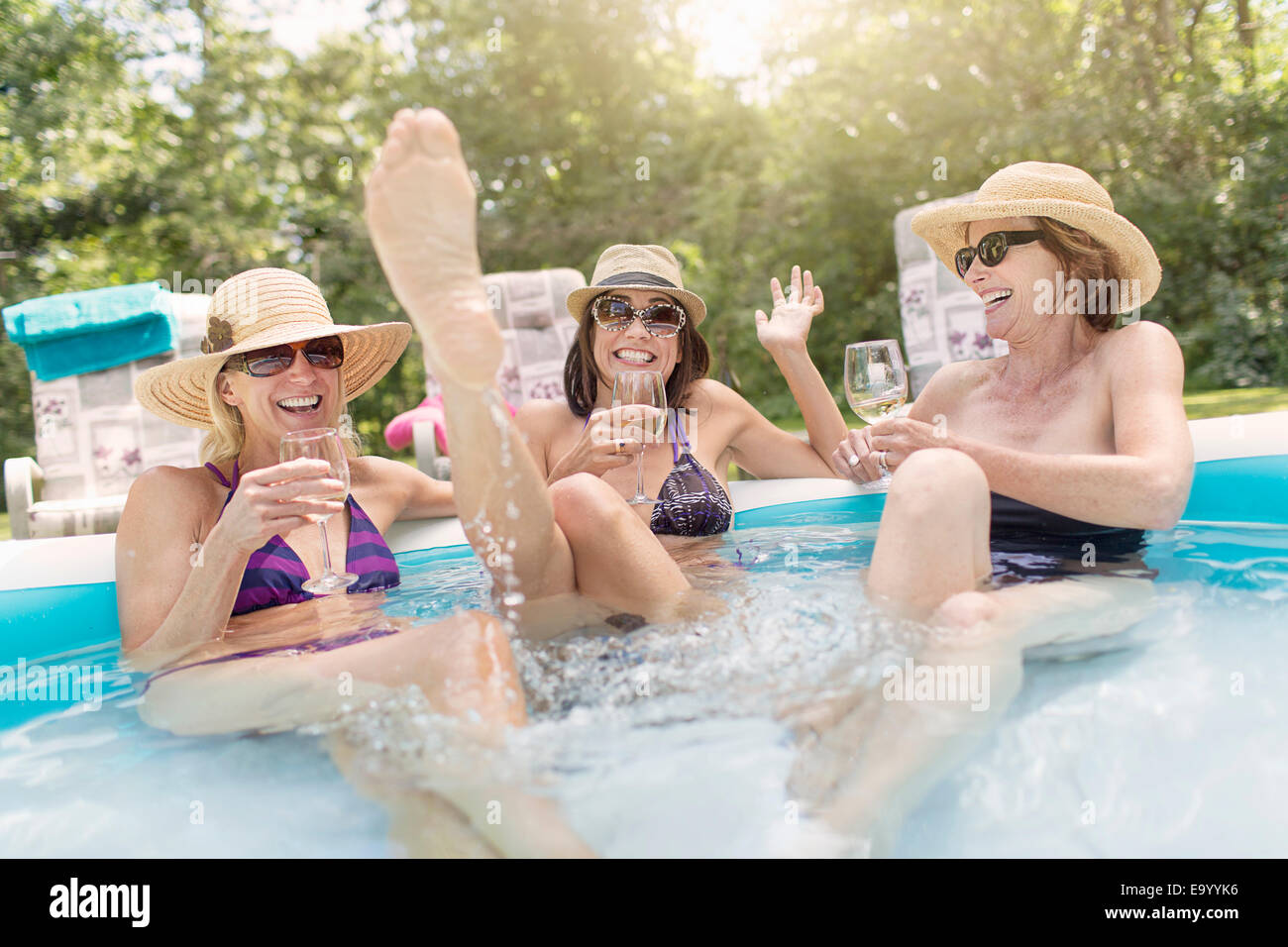 Three mature women sitting in paddling pool, drinking wine - Stock Image