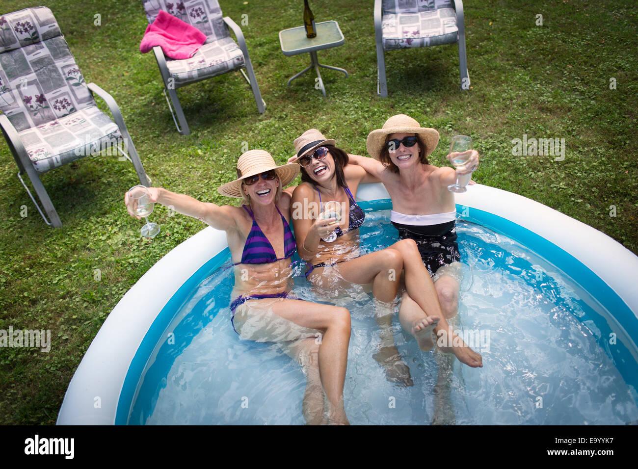 Three mature women sitting in paddling pool, drinking wine, elevated view Stock Photo