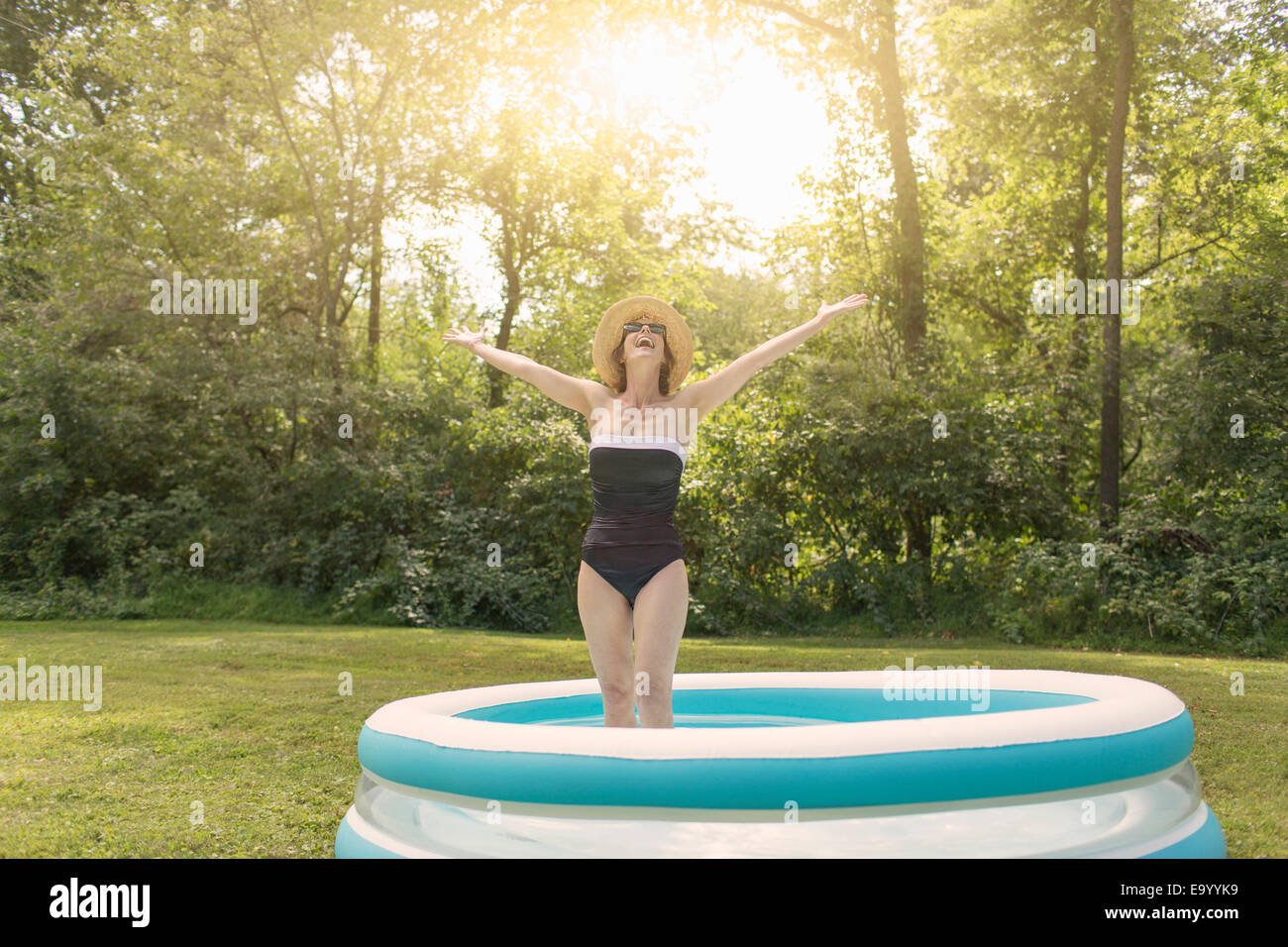 Mature woman standing in paddling pool, arms outstretched - Stock Image
