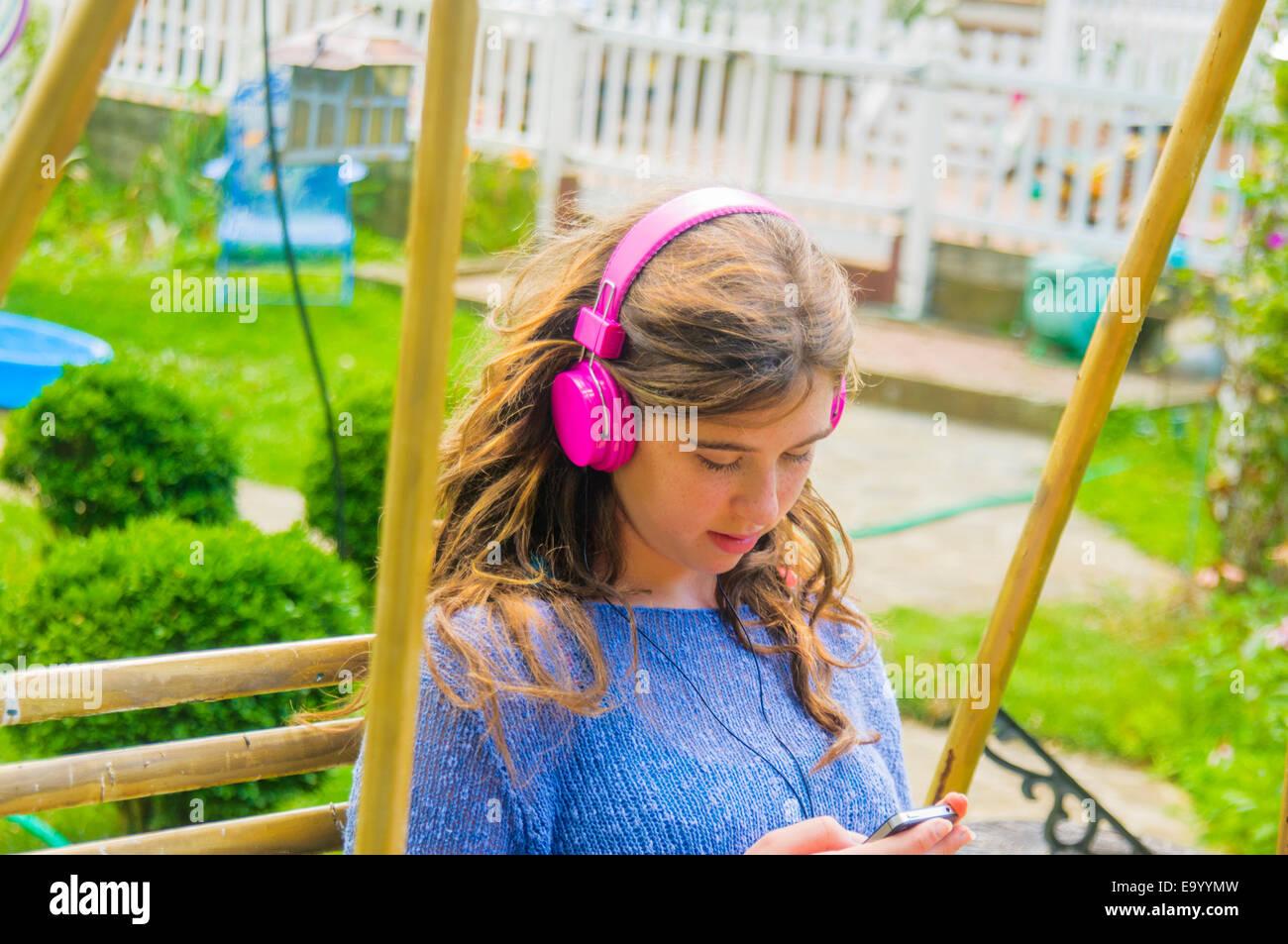 Teenage girl sitting outdoors, wearing headphones Stock Photo