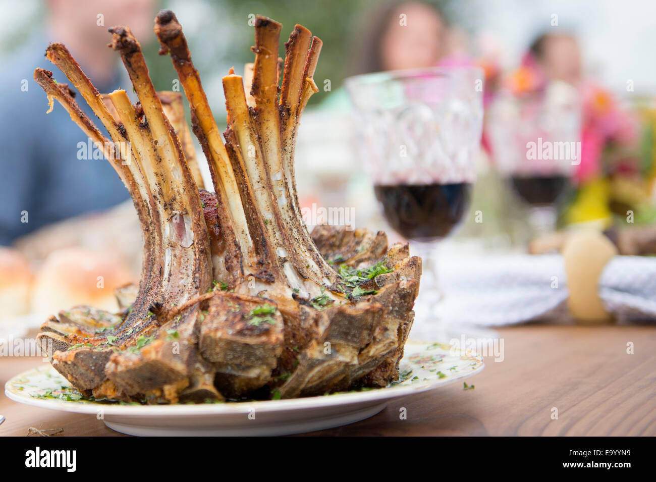 Rack of lamb on plate at family meal, close-up - Stock Image