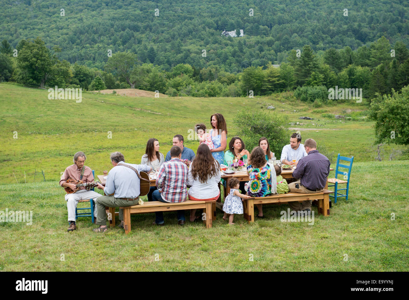 Family having meal together and socialising, outdoors - Stock Image