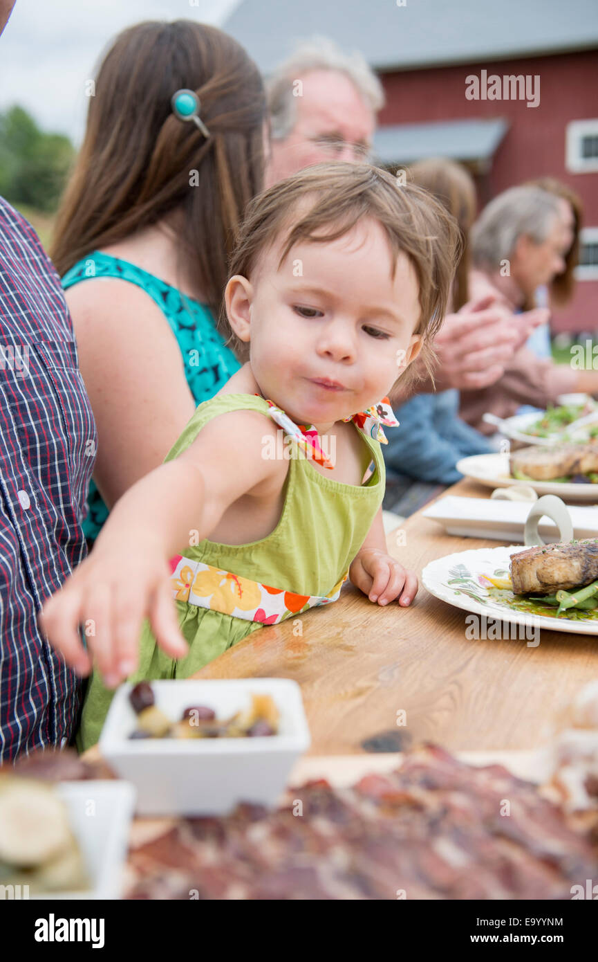 Young child picking olive from dish at family meal, outdoors - Stock Image
