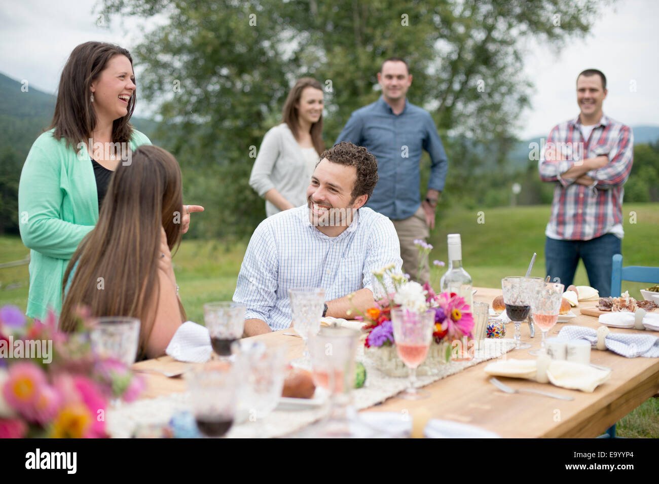 Family and friends gathered around, talking, at the end of a meal, outdoors - Stock Image