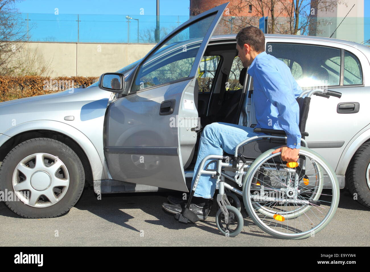 Wheelchair user getting into a car - Stock Image