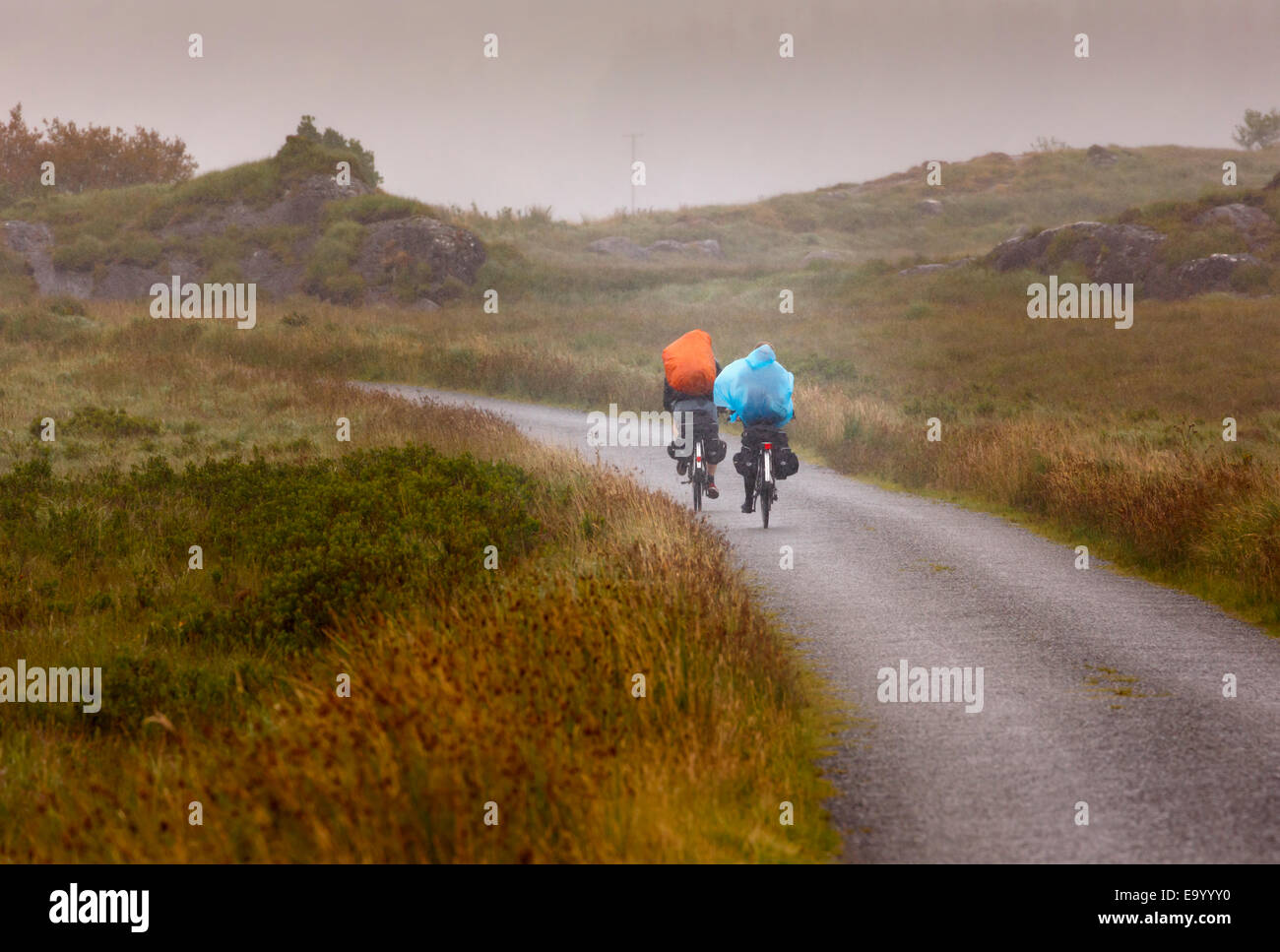 near Derrylea, County Kerry, Republic of Ireland.  Eire.  Ecotourism.  Two touring cyclists press on through the - Stock Image