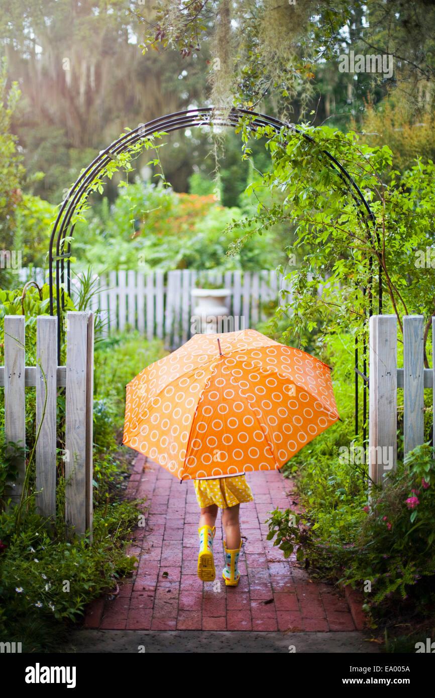 Girl walking through garden gate carrying umbrella Stock Photo