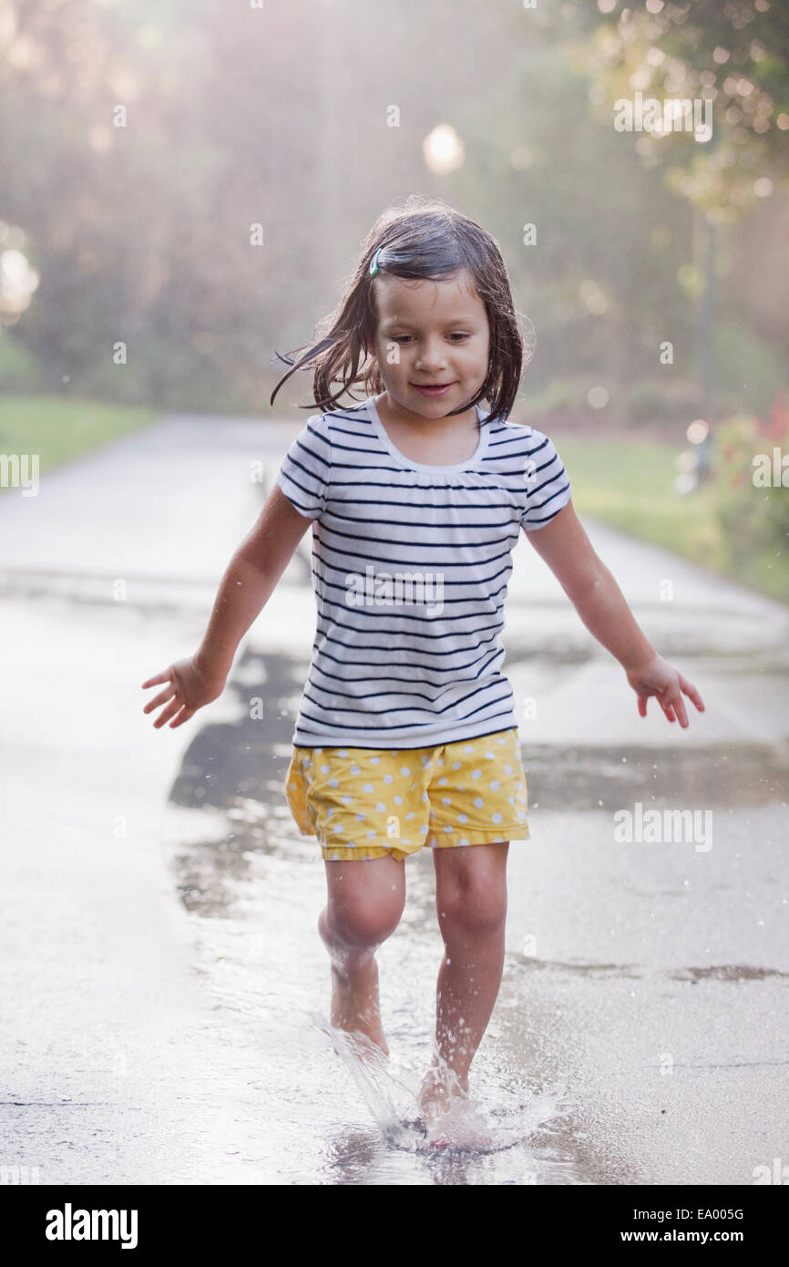 Barefoot girl running through puddles on rainy street - Stock Image