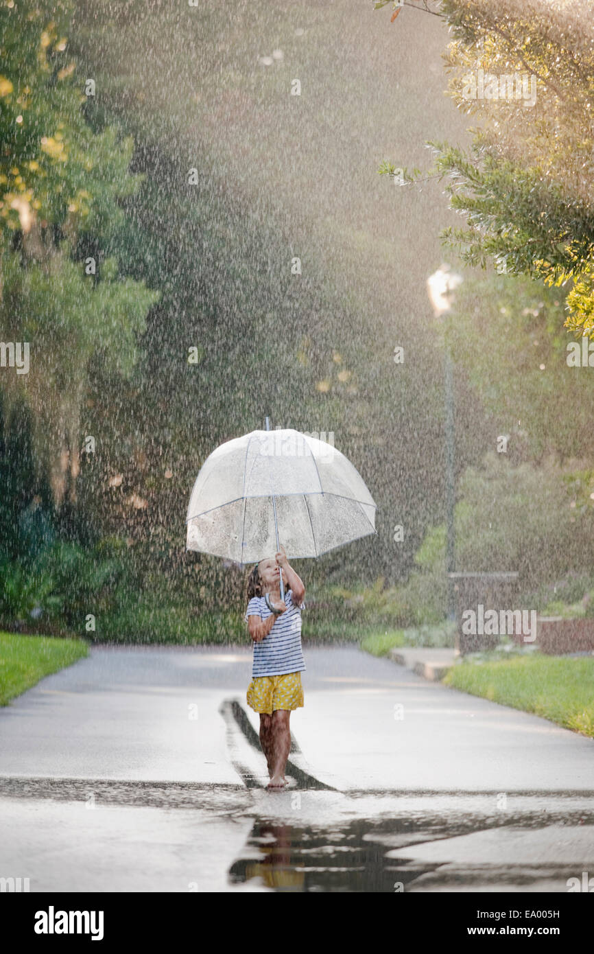 Barefoot girl holding up umbrella and walking through puddles on street - Stock Image