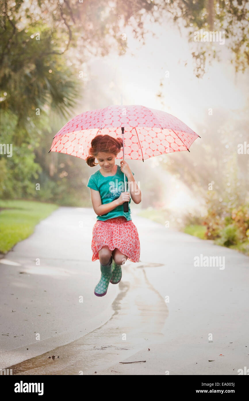 Girl holding up umbrella and jumping puddles on street - Stock Image