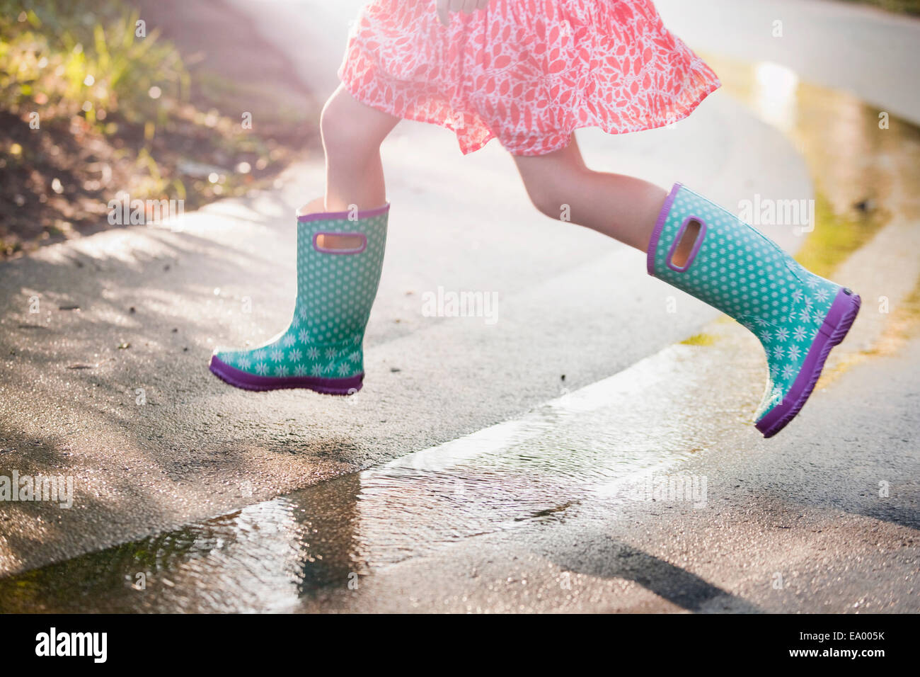 Waist down view of girl jumping puddles on rainy street - Stock Image
