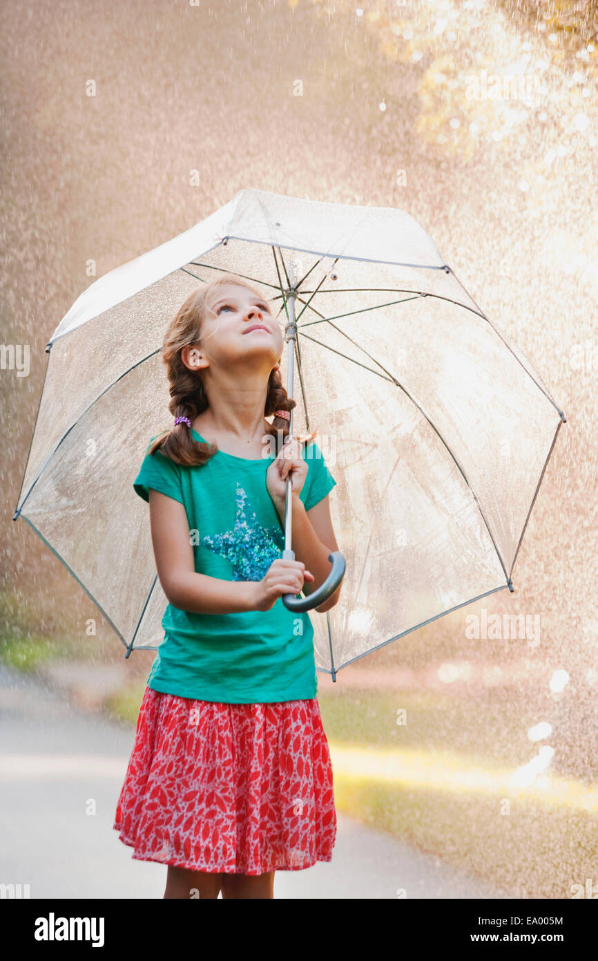 Girl holding up umbrella on rainy street - Stock Image
