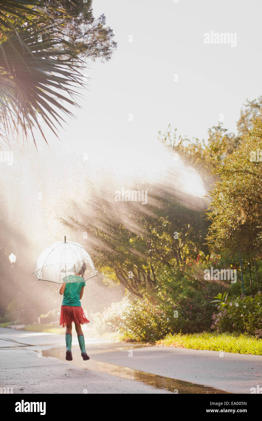 Rear view of girl holding up umbrella and jumping puddles on street - Stock Image