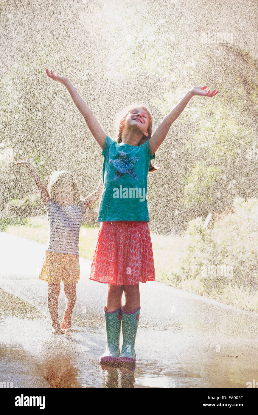 Two girls with arms open standing in water spray on street - Stock Image