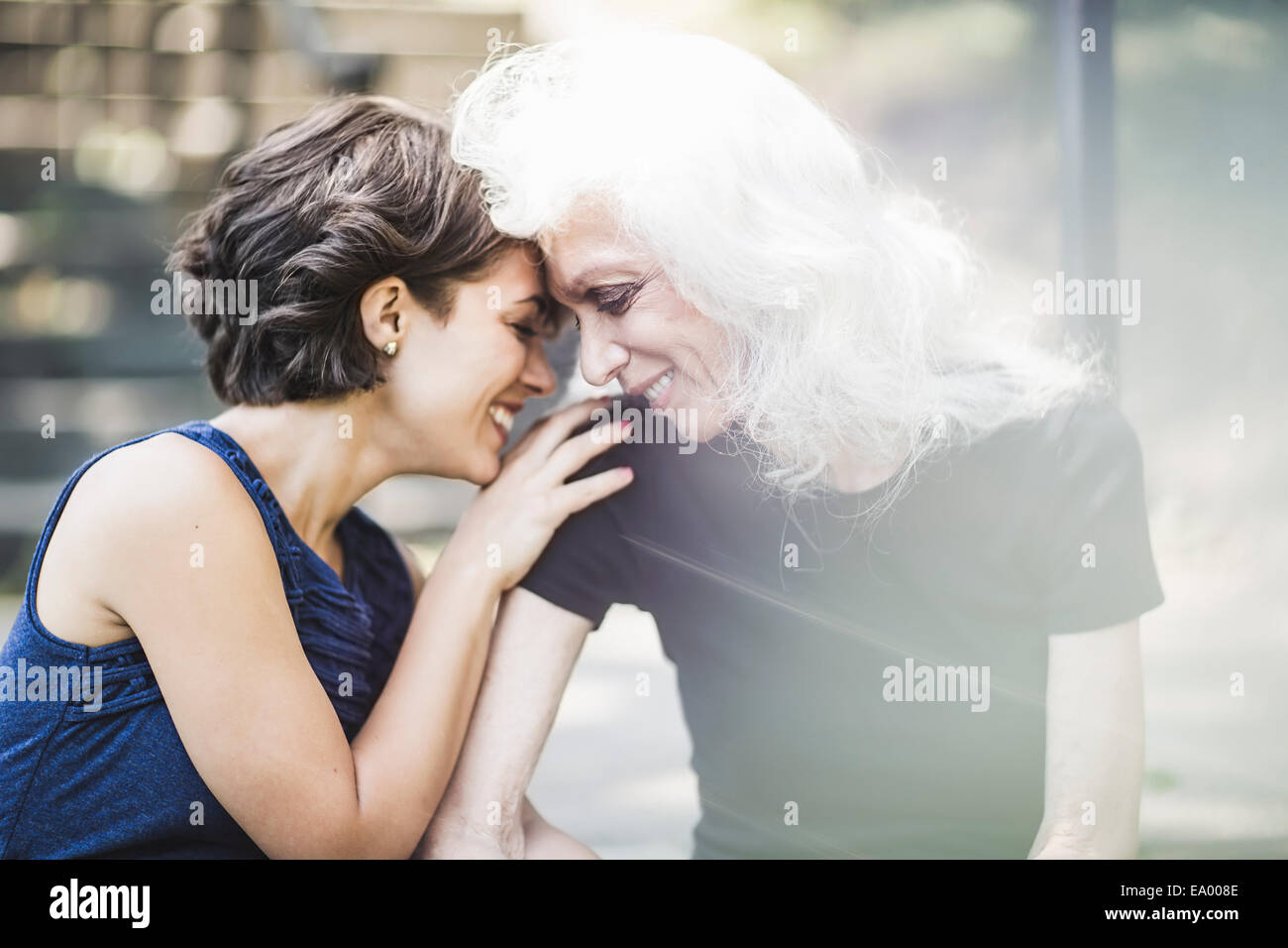 Young woman sharing tender moment with mentor - Stock Image