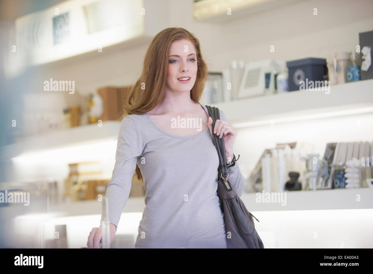 Woman walking past products on display shelves - Stock Image