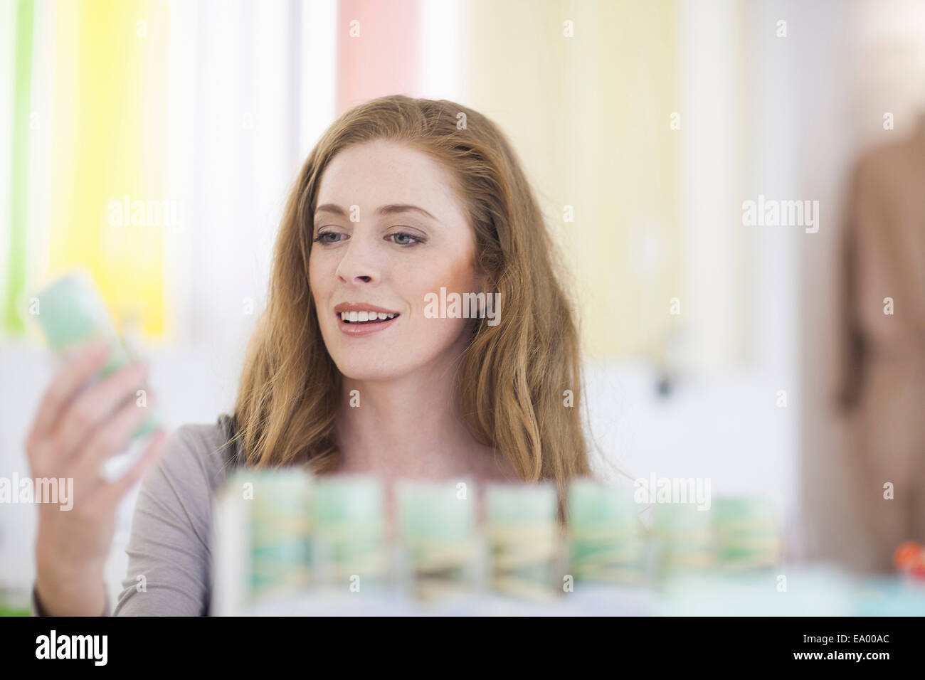 Woman browsing products on display shelf - Stock Image