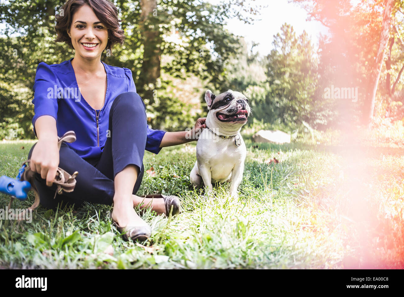 Young woman with dog in city park - Stock Image