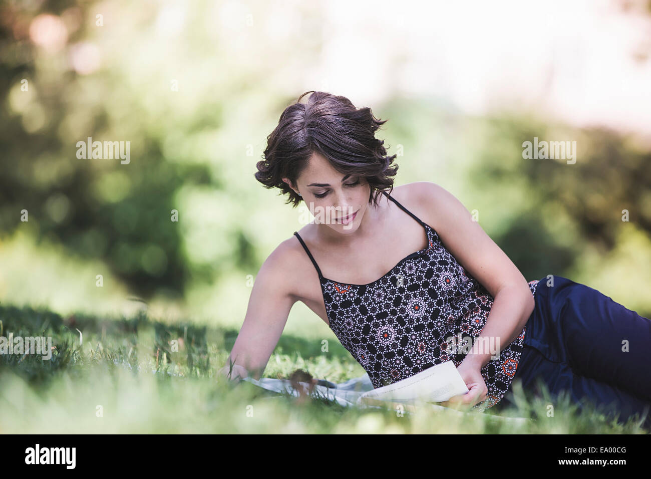 Young woman sitting in city park studying textbook - Stock Image
