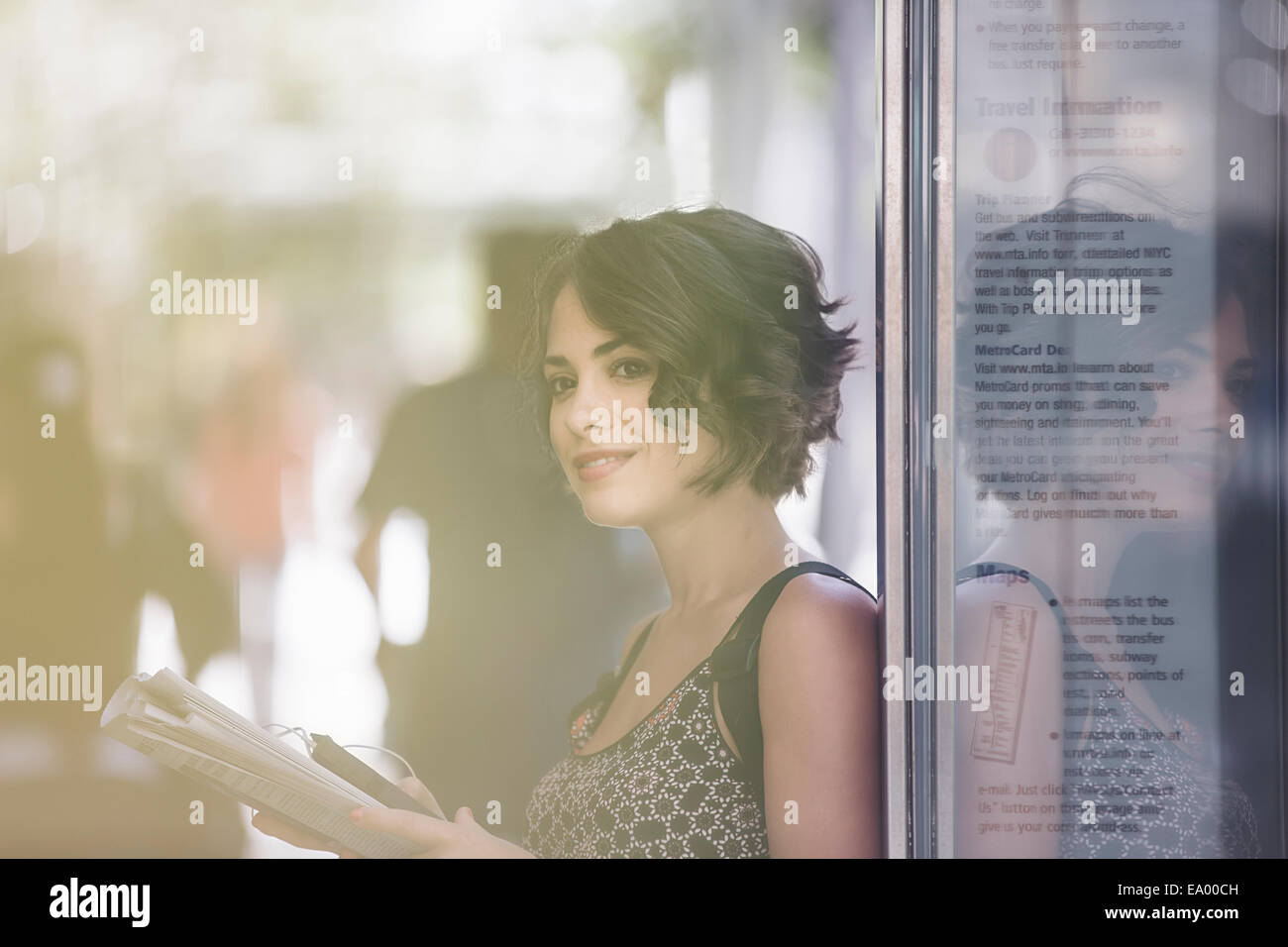 Young woman at bus stop reading newspaper and waiting for bus, New York, US - Stock Image