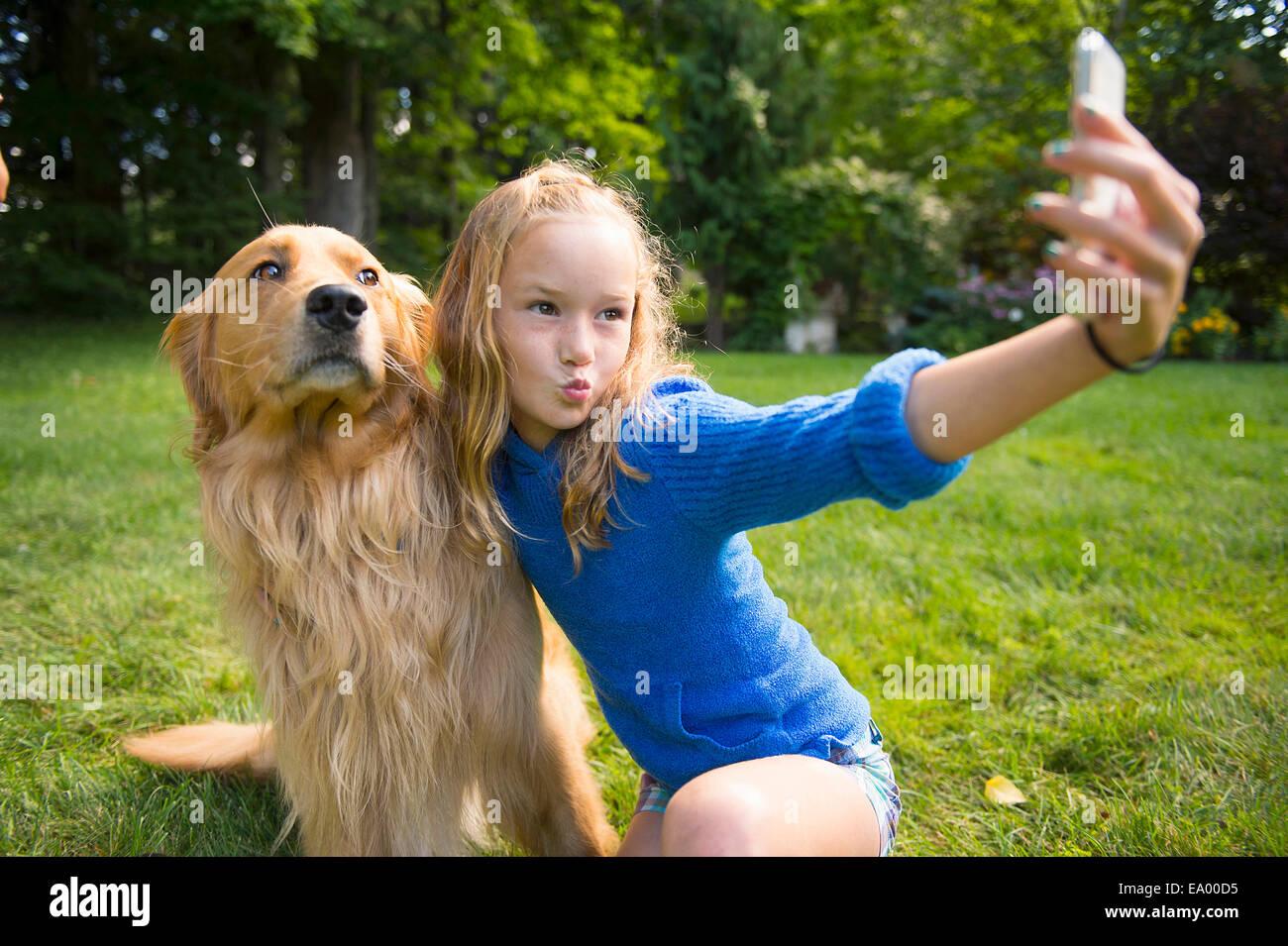 Girl taking selfie with pet dog in garden - Stock Image