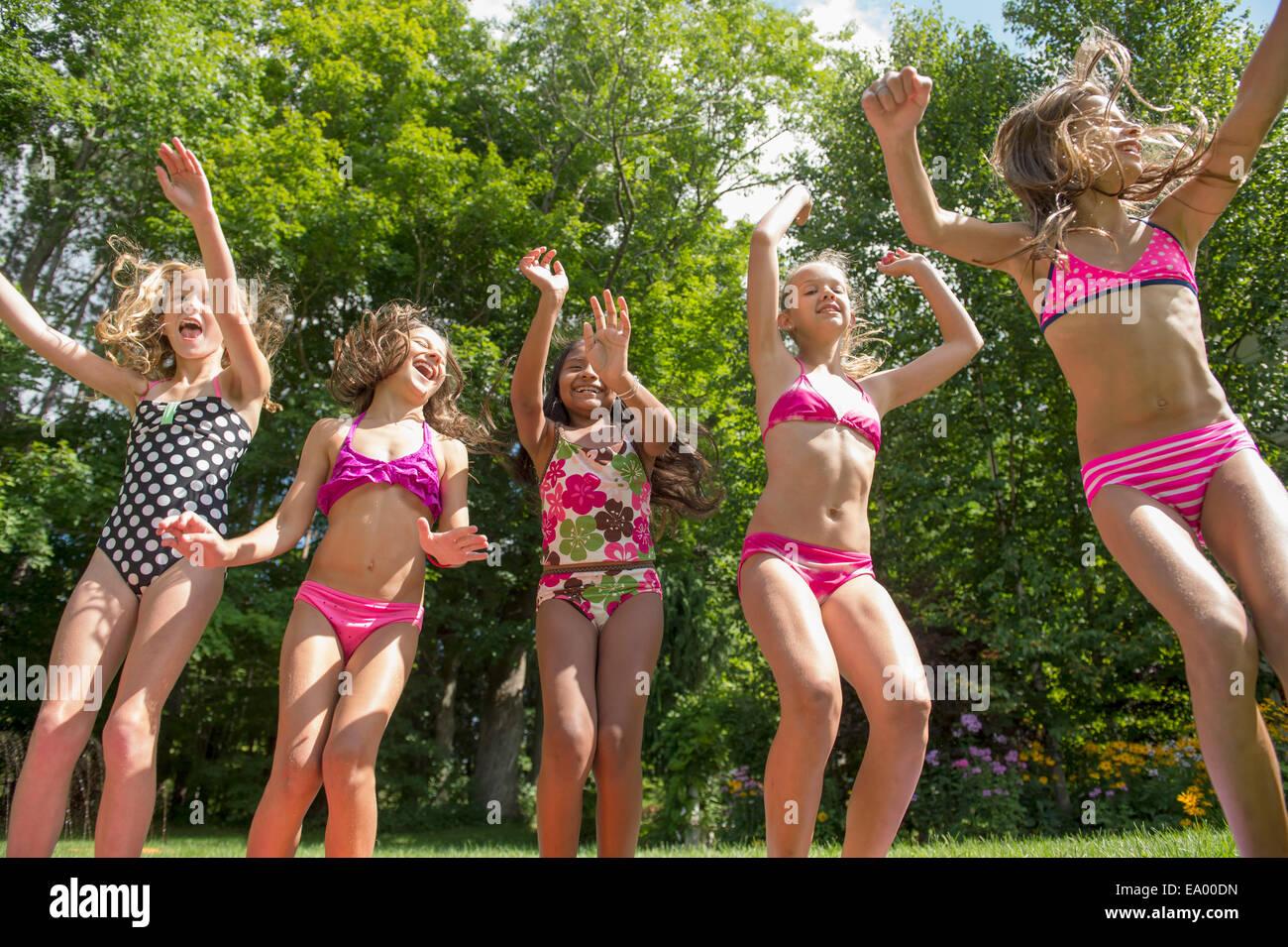 Girls In Swimming Costume Jumping In Garden