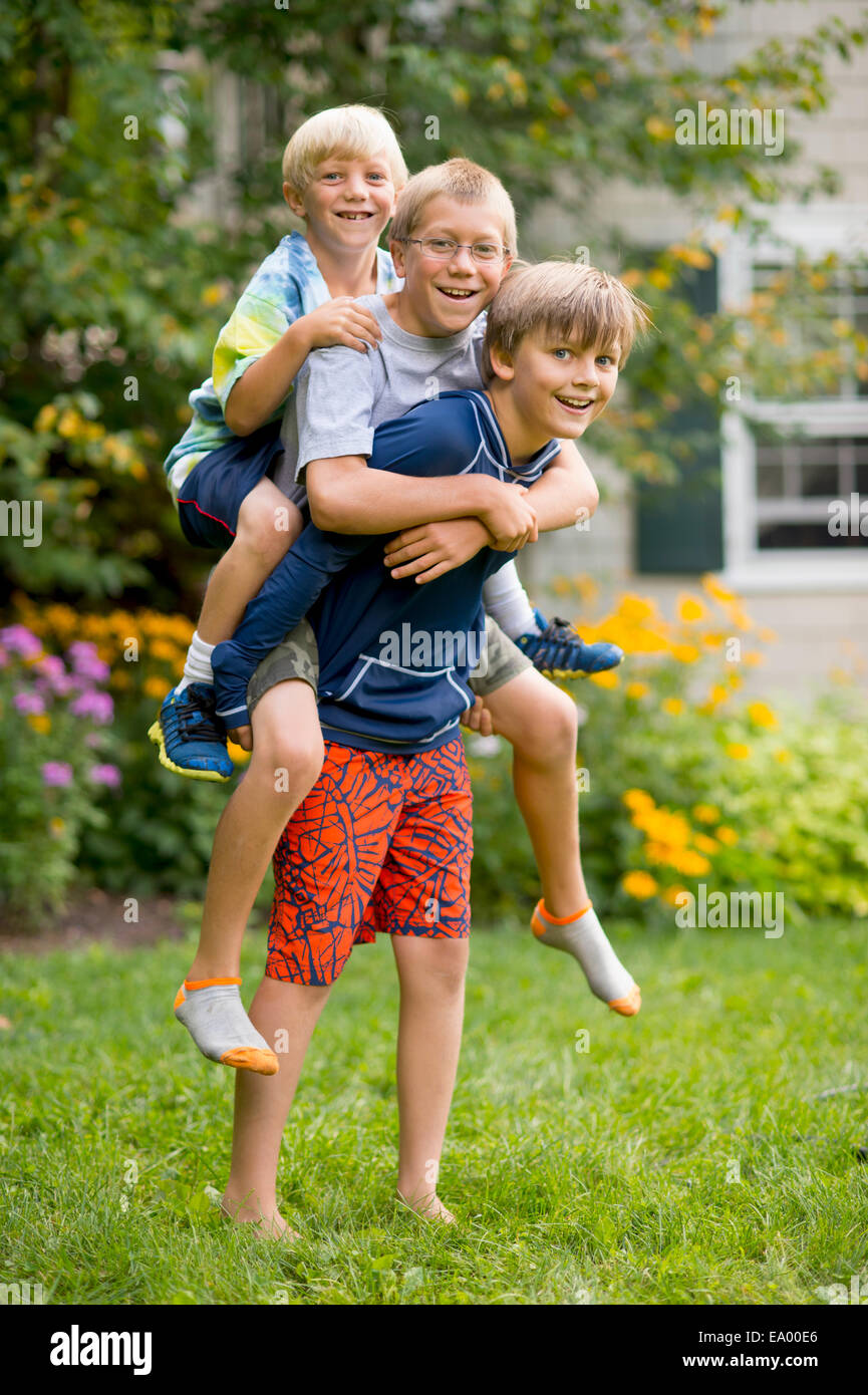 boys playing piggyback  garden stock photo