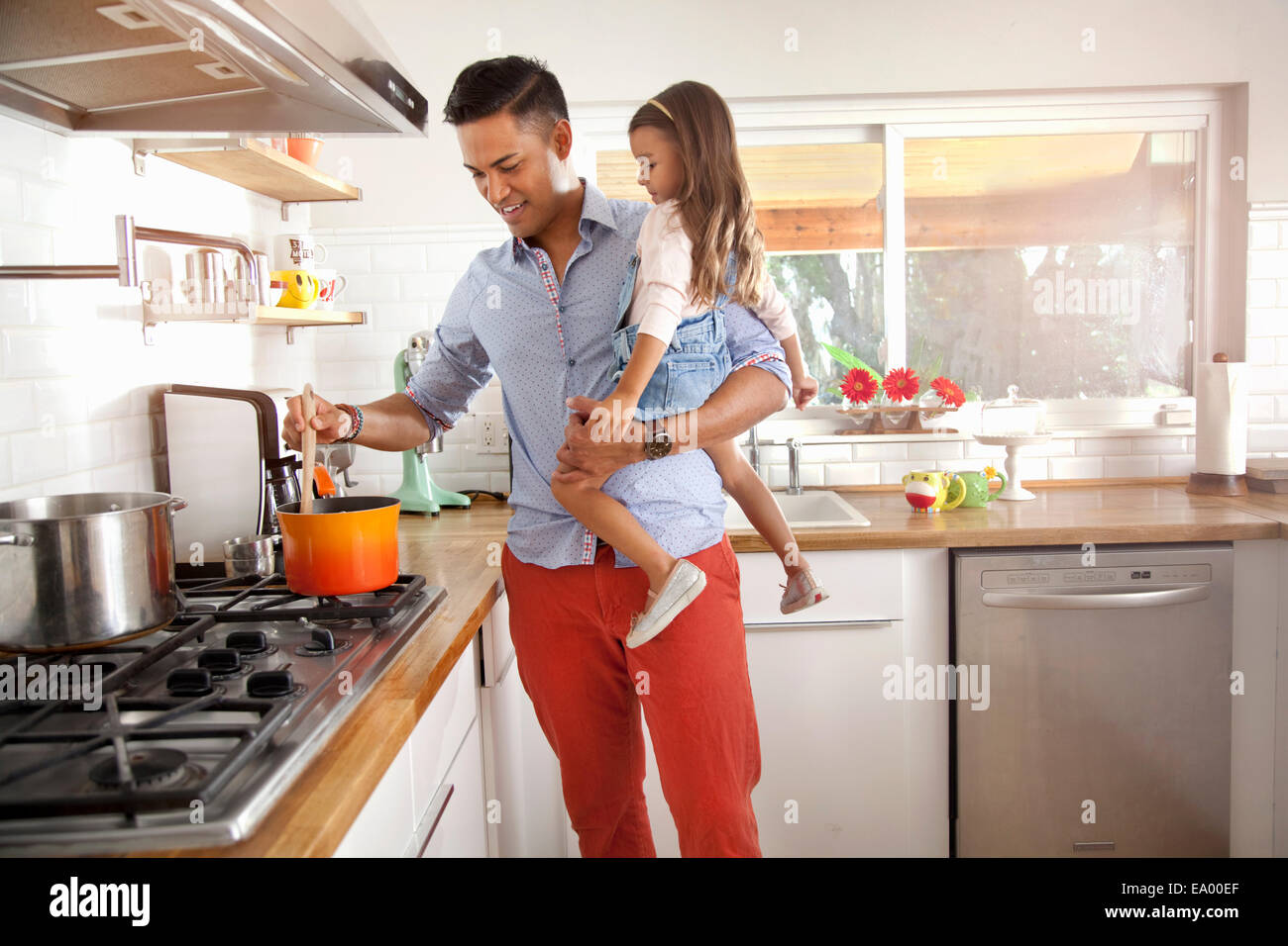 Father and daughter cooking in kitchen - Stock Image