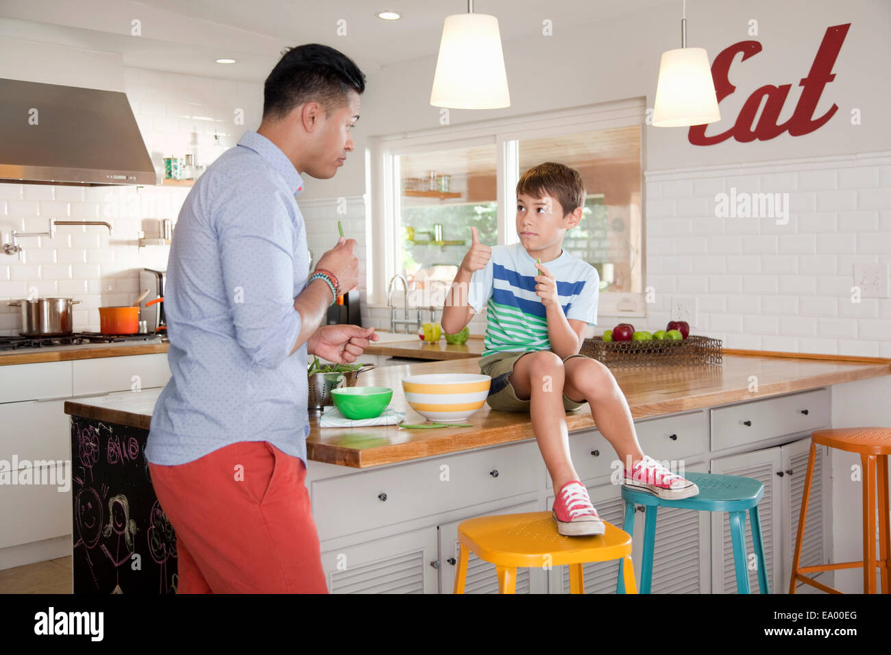 Father and son in kitchen, boy sitting on counter Stock Photo