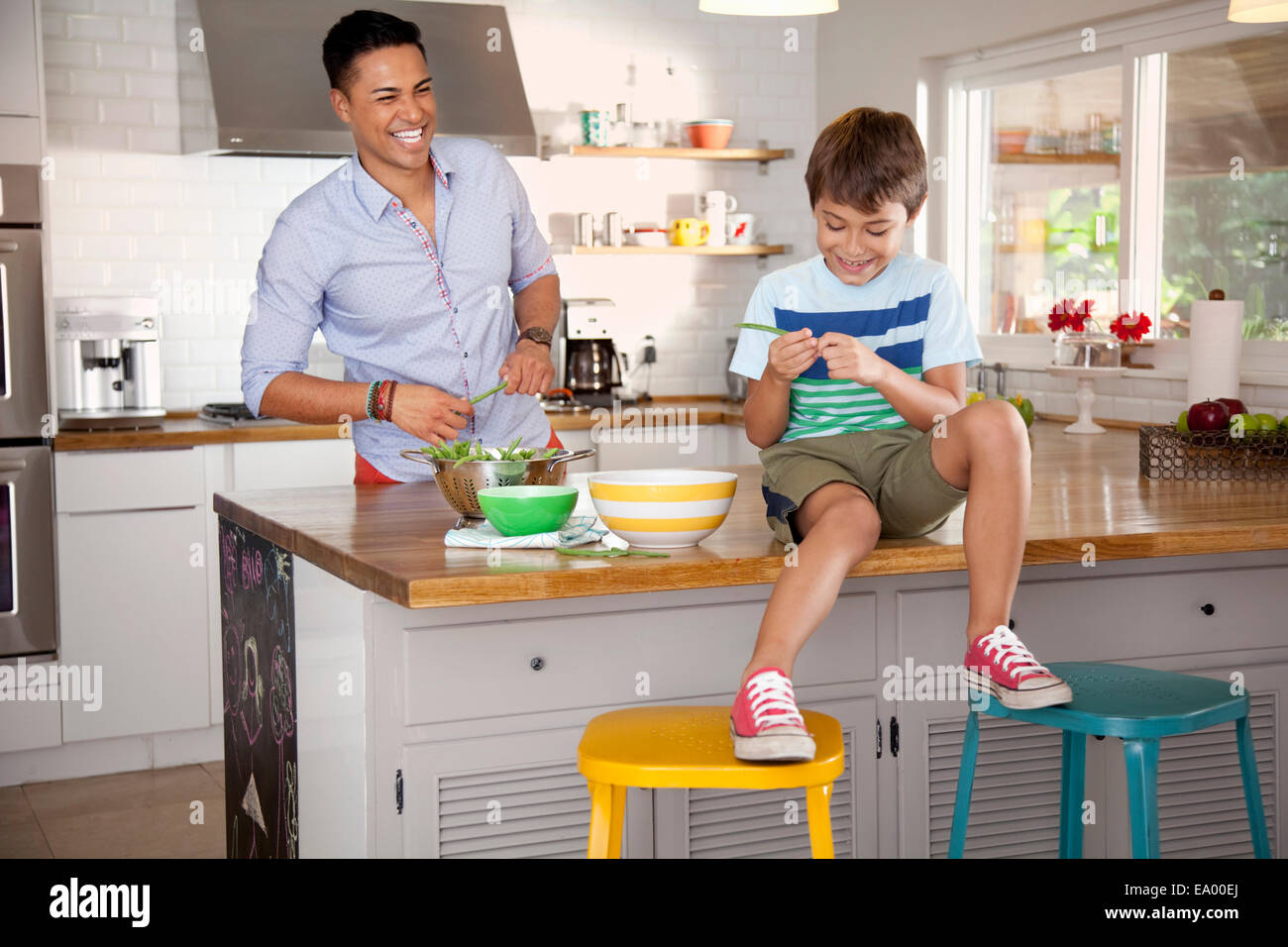 Father and son in kitchen, boy sitting on counter - Stock Image