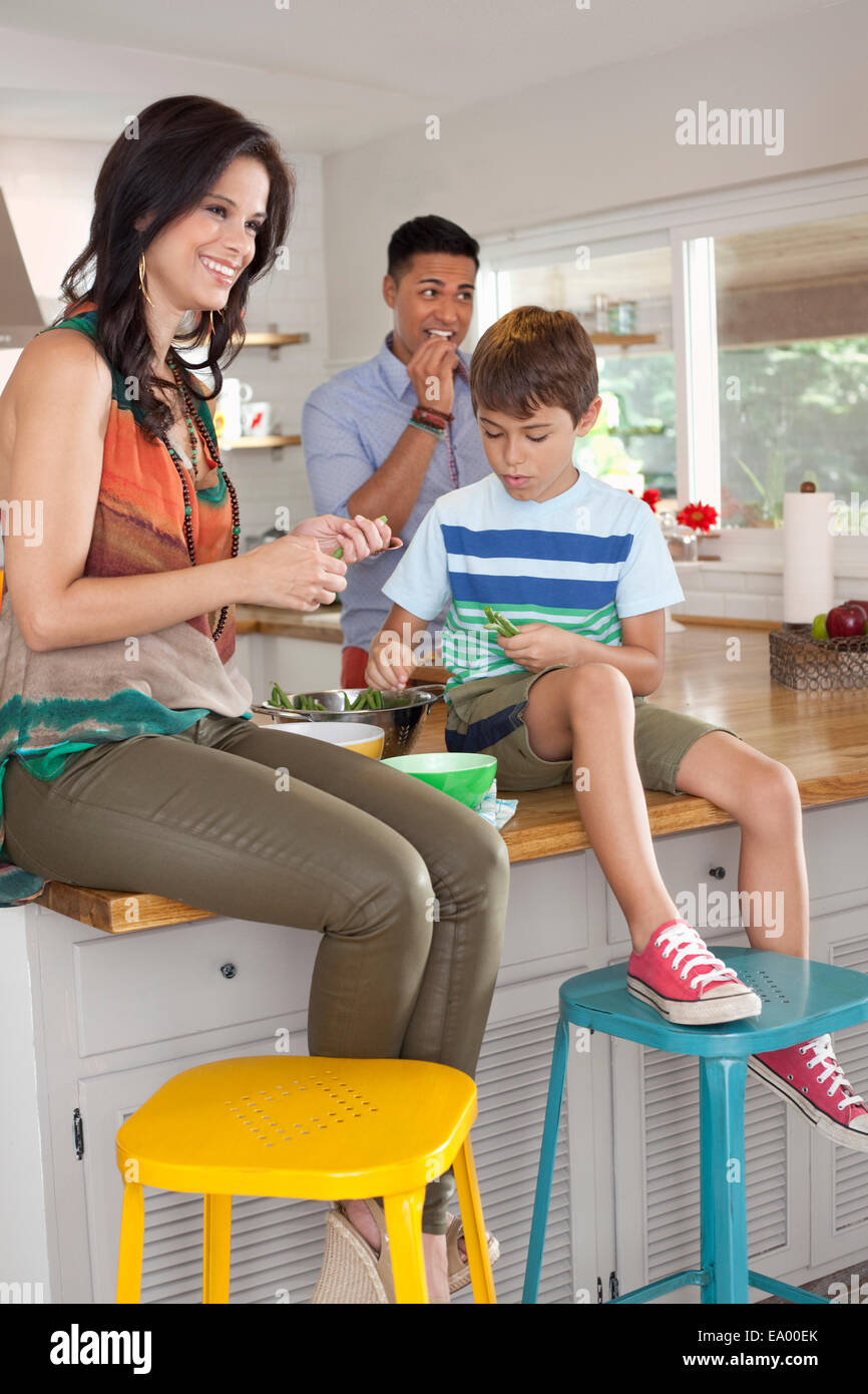 Boy sitting on kitchen counter with mother and father - Stock Image