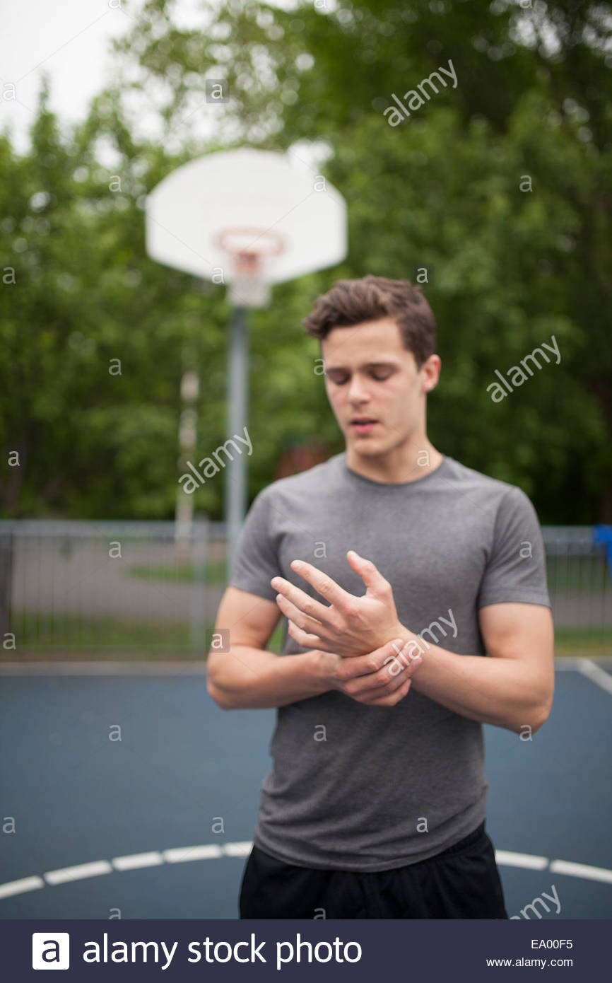 Young man holding wrist on basketball court - Stock Image