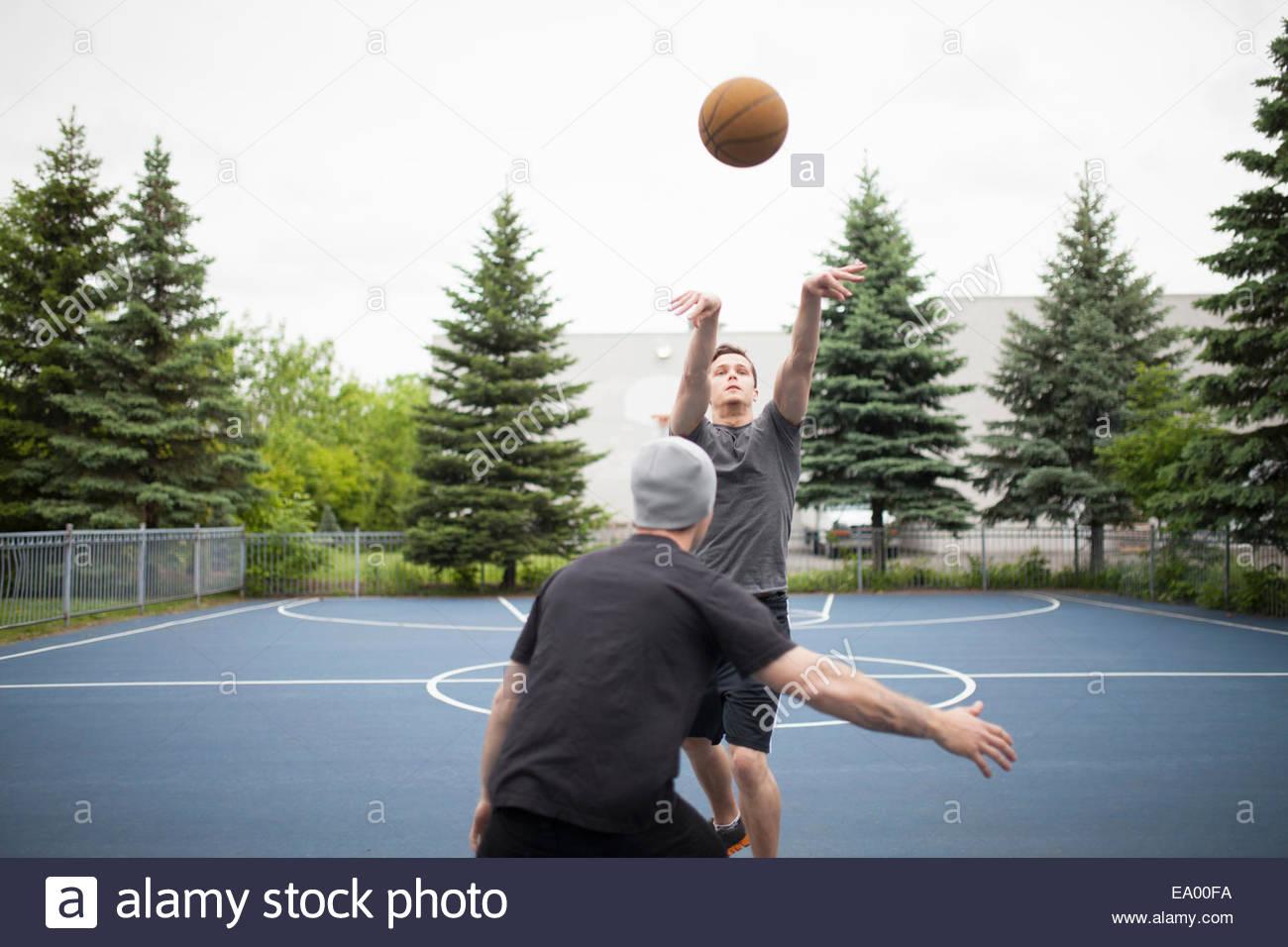 Young men playing basketball - Stock Image