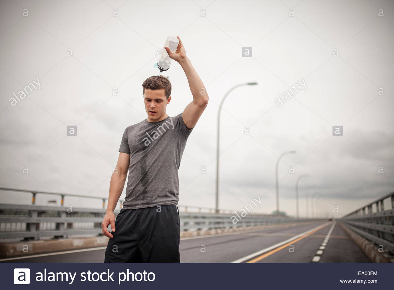 Young man pouring water over head - Stock Image