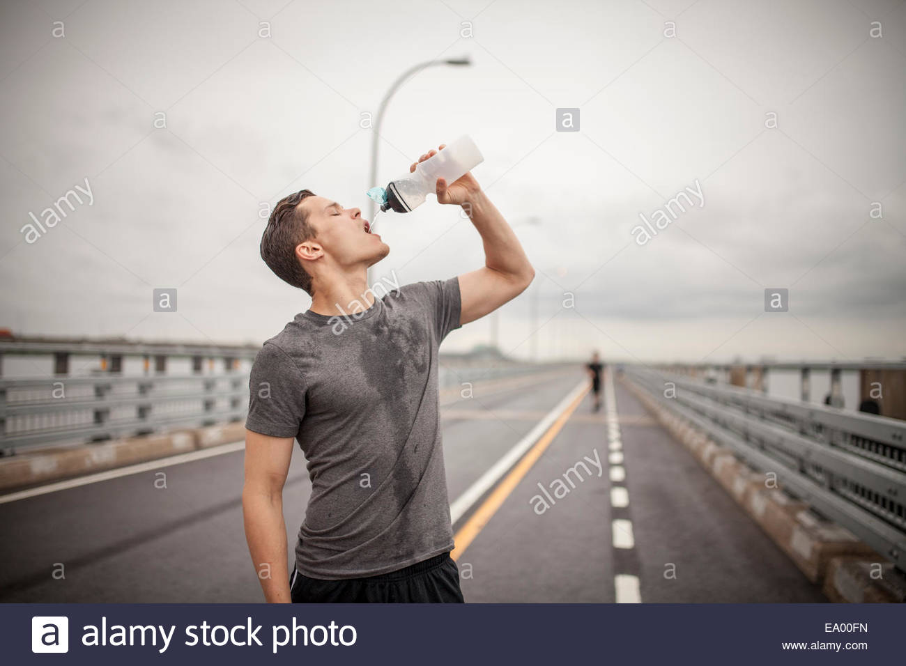 Young man drinking water from bottle - Stock Image