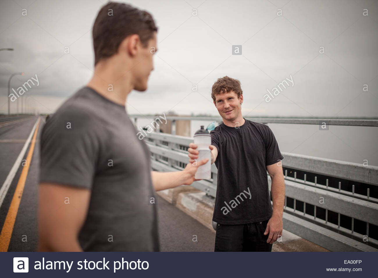 Young man handing water bottle to friend - Stock Image