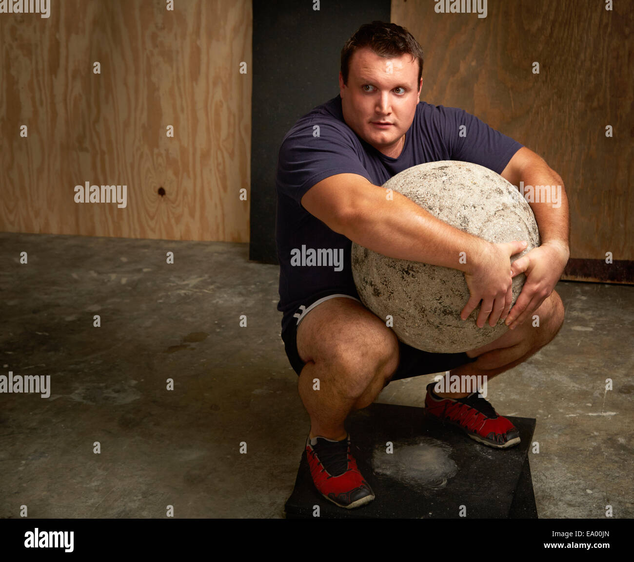 Portrait of young male weightlifter squatting with atlas ball in gym - Stock Image