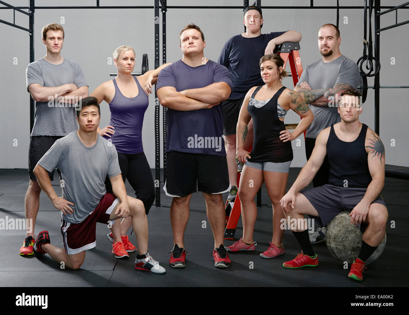 Portrait of eight men and women in gym - Stock Image