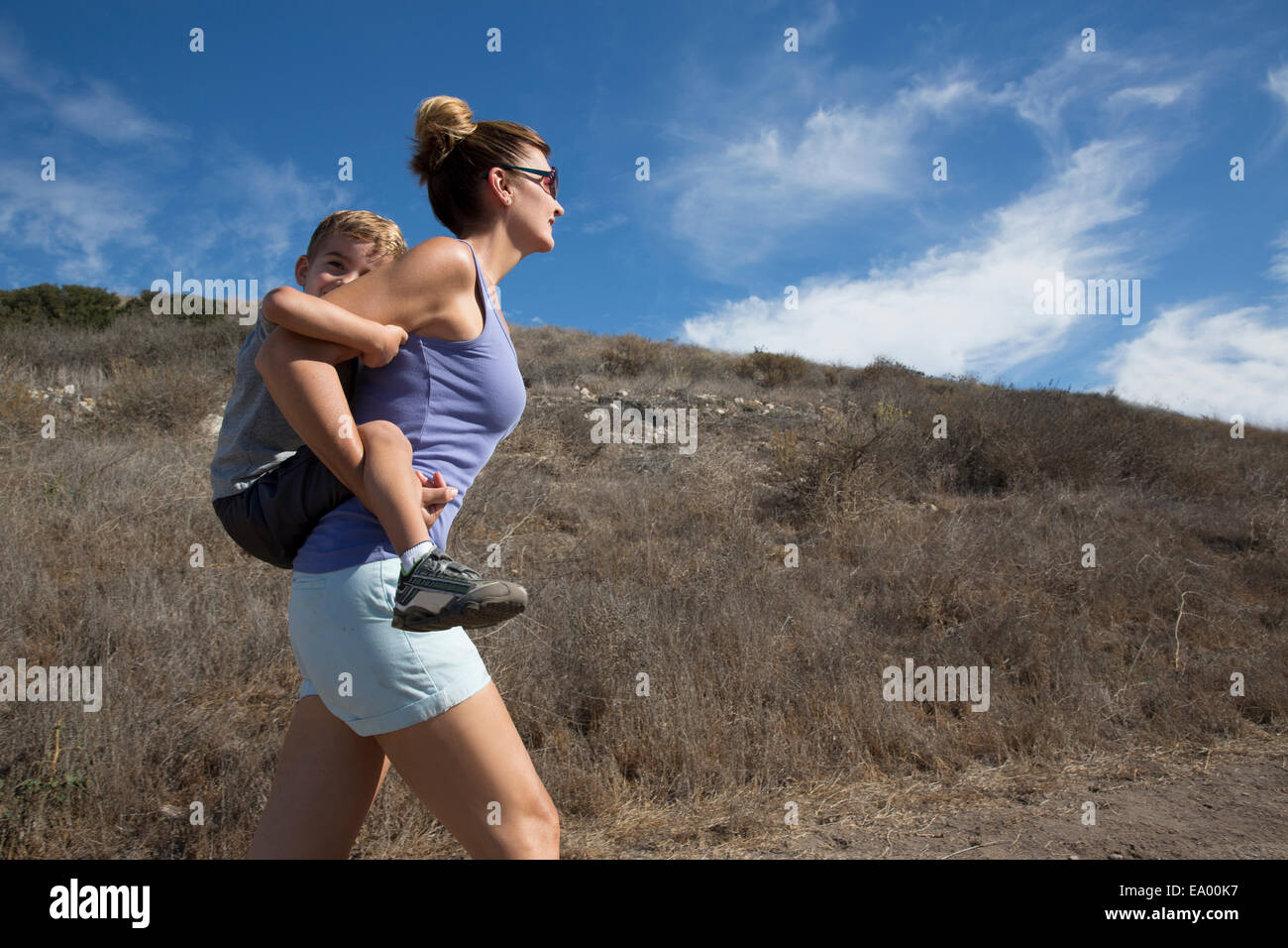 Mature woman giving son a piggy back up hill, County Park, Los Angeles, California, USA - Stock Image