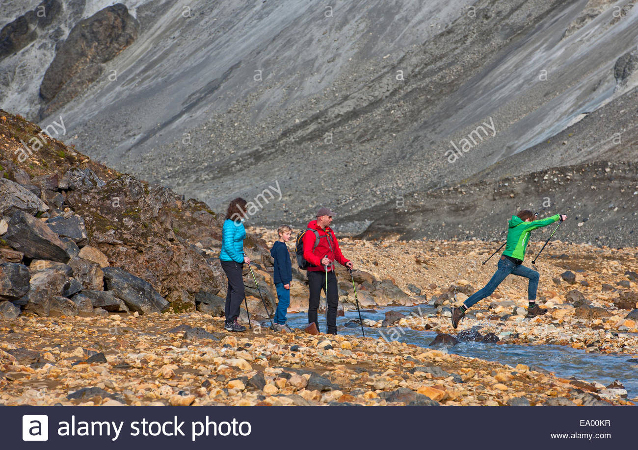Family crossing the river next to Graenagil at Landmannalaugar, Fjallabak, Iceland - Stock Image