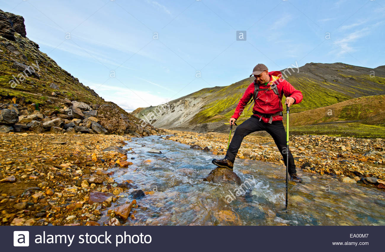 Hiker crossing river at Landmannalaugar, Fjallabak, Iceland - Stock Image