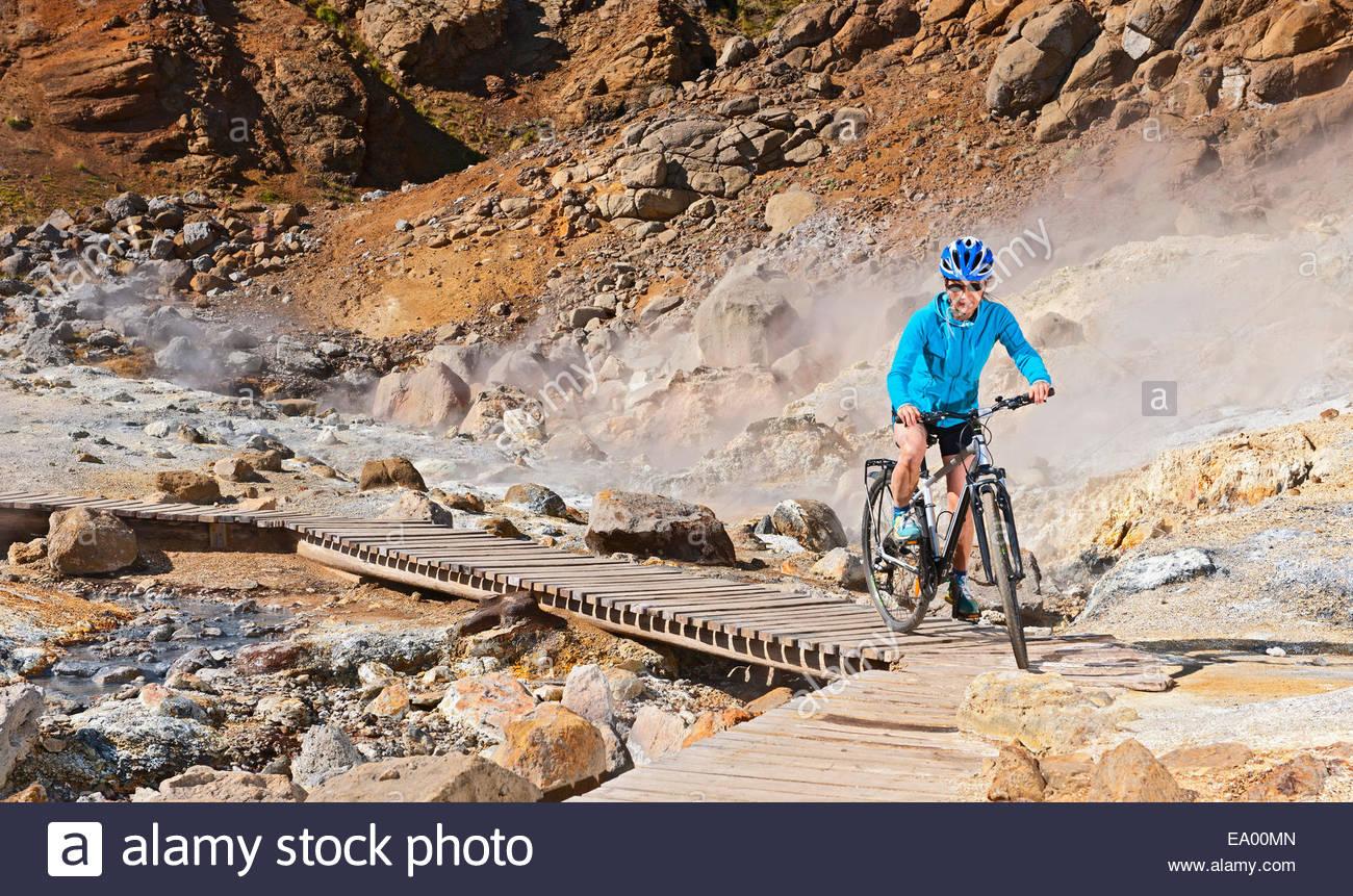 Mature female cyclist riding hybrid bike at geothermal site, Krysuvik, Reykjanes, Iceland - Stock Image