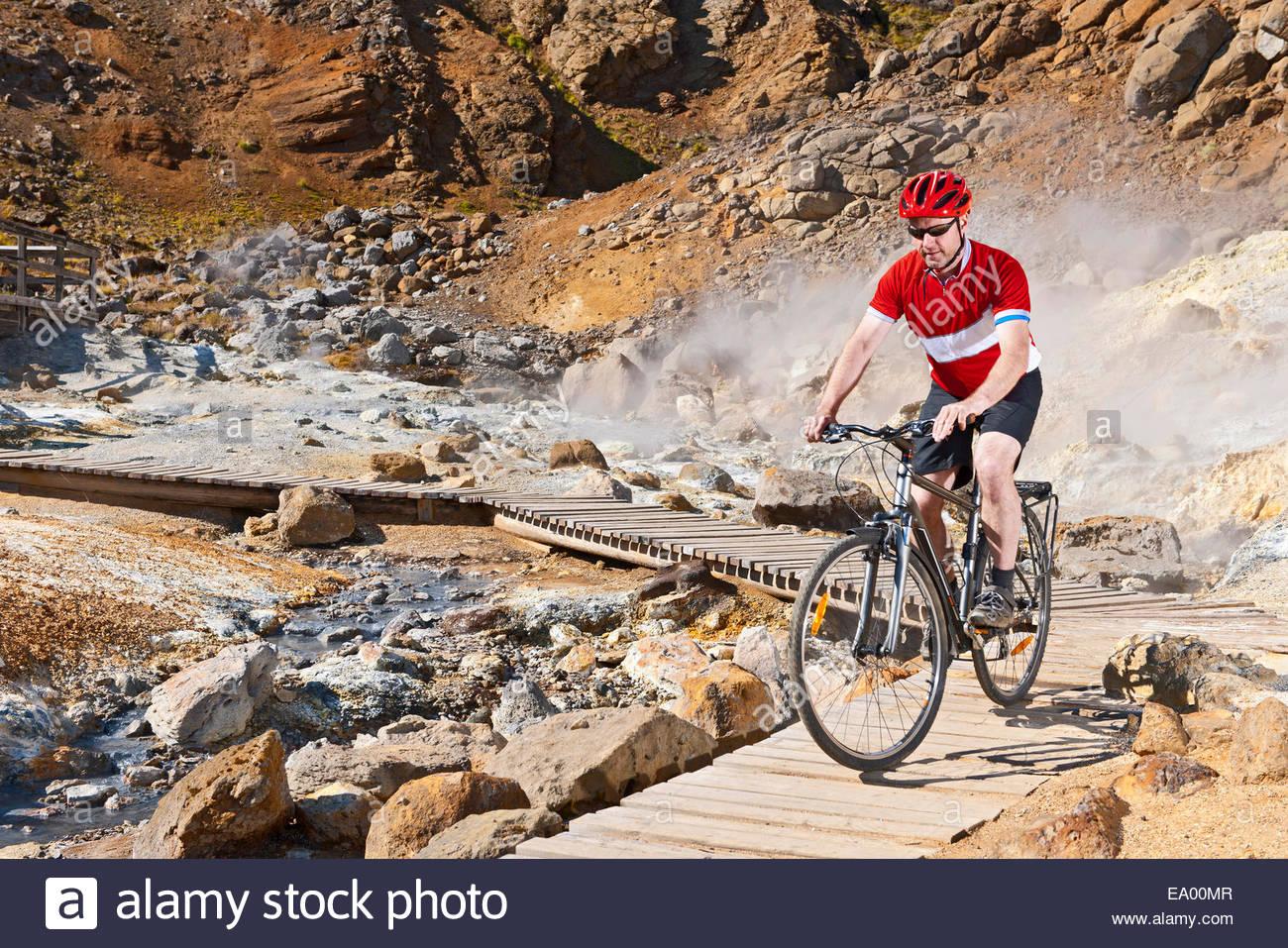 Mature male cyclist riding hybrid bike at geothermal site, Krysuvik, Reykjanes, Iceland - Stock Image